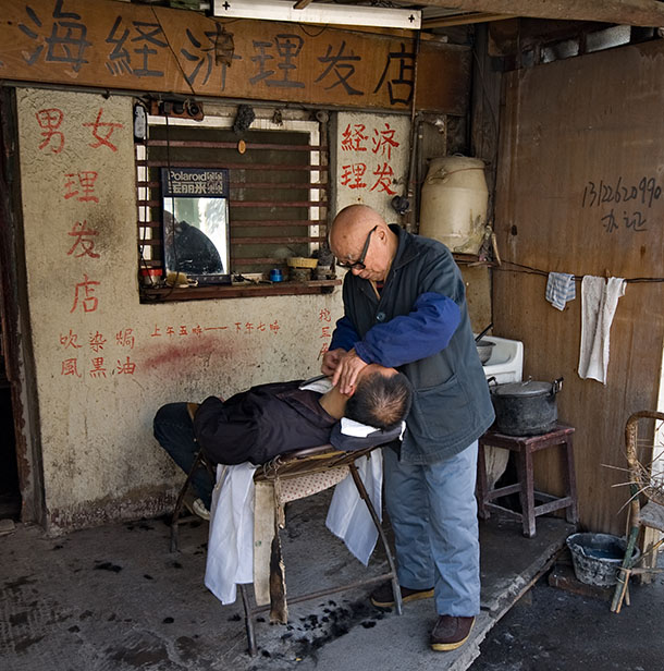 A barber, working on the street, in front of his shop. Shanghai, February 2006.